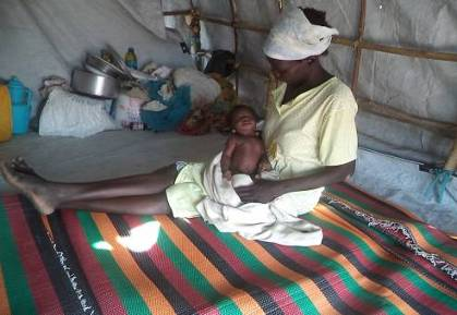 Monica and her 1 month old baby Don Bosco (named after the Church who took her in!), in the tent that is her new home.
